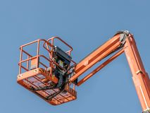 Single Orange Cherry Picker. Machinery against a blue sky stock photo