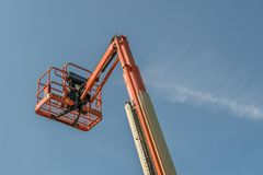 Single Orange Extended Cherry Picker. Against a blue sky stock photo