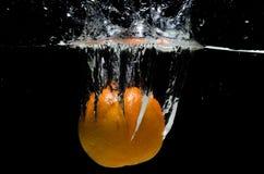 Orange splashing in the water Stock Photos