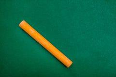 Single orange piece of chalk on green Stock Photos