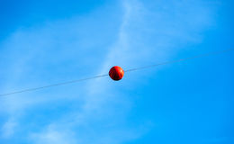 Single orange warning sphere on cable against sky Stock Images