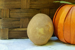 A single organic russet potato sits by a fake pumpkin and a wick Royalty Free Stock Photography