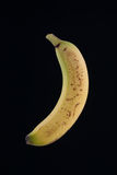Single organic spotted banana isolated on black Stock Photo