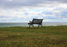Single Outdoor Iron Bench at Ocean with Clouds Stock Photography