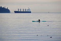 Single Paddler and Large Ocean Freighter. A single paddler rows his canoe across the open waters with a freighter in the background Stock Photo