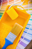Single paint brush in tray with roller on color Royalty Free Stock Photography