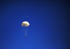 Single parachute jumper against blue sky background Stock Image