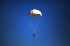 Single parachute jumper against blue sky background Royalty Free Stock Photography