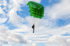 Single parachute jumper on a wing parachute on blue sky backgrou Stock Photos