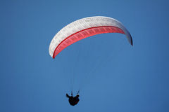 Single paraglider against a blue sky. A Singlearaglider flying against a blue sky backlit by the sun Stock Photo