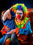 Single parent family. Mom after work birthday clown. Adult child relationship. Single parent family. Tired mom after work as clown on birthday on dark Stock Photos