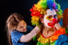 Single parent family. Mom after work birthday clown. Adult child relationship. Single parent family. Tired Halloween mom after work as clown on birthday on dark stock images