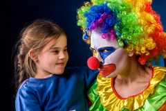 Single parent family. Mom after work birthday clown .Adult child relationship. Single parent family. Tired mom after work as clown on birthday on dark stock images