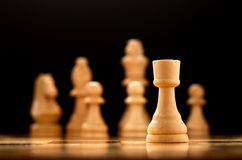 Single pawn on a chessboard. Low angle view of a single wooden chess piece, the pawn, on a chessboard with the rest of the pieces visible in the background Stock Images