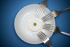 One pea and many forks royalty free stock photos