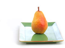 Single Pear on Simple Green Dish Stock Photography