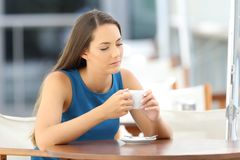 Pensive sad lady in a coffee shop Stock Images