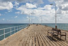 Single person at the end of long wooden  jetty with benches and. Lamps.  Springtime shot showing the jetty and the sea Royalty Free Stock Images