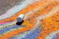 Single Piece of Chalk on Sidewalk Art. A single piece of sidewalk chalk sits on the ground on top of bright colorful chalk art royalty free stock photography