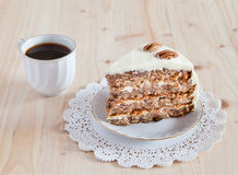 A single piece of Hummingbird cake with pecans. And cream cheese frosting with coffee on the wooden table royalty free stock photo