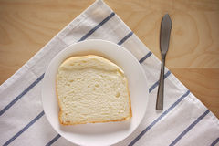 Single piece of white bread on table top Stock Photos