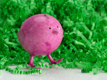 Pink baby chick statue with green shredded crinkle Royalty Free Stock Image