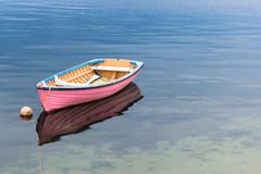 A single pink boat in clear blue water. A single pink boat with a reflection in clear blue water Stock Photos