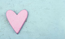 Single pink heart on light blue wooden background