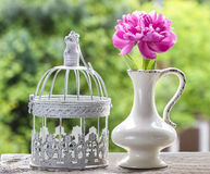 Single pink peony flower in white ceramic vase. And vintage decorative cage on rough rustic wooden table in lush spring garden Royalty Free Stock Photography