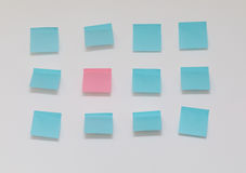 Single pink post it note in sea of blue post it notes. On a white background Royalty Free Stock Photos
