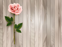 Single pink rose on an old wooden background. Stock Photos