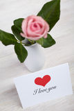 Single pink rose in porcelain vase on wooden table and I love you card Royalty Free Stock Photo