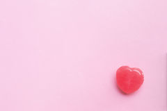 Single Pink Valentine`s day heart shape candy on empty pastel pi. Nk paper background. Love Concept. top view. Minimalism colorful hipster style Stock Photography
