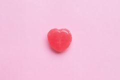 Single Pink Valentine`s day heart shape candy on empty pastel pink paper background. Love Concept. top view. Minimalism colorful Stock Images