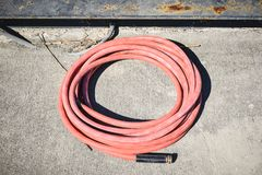 Single Pink watering hose coiled on sidewalk. Pink watering hose coild isolated on sidewalk stock photos