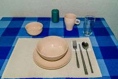 Single place setting on blue checked table cloth. Single place setting of plate,soup bowl, rice bowl, cup and glass with fork spoon and chop sticks on peach Royalty Free Stock Image