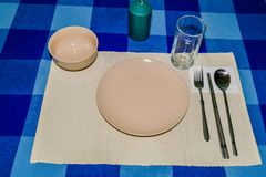 Single place setting on blue checked table cloth. Single place setting of plate, rice bowl,and glass with fork spoon and chop sticks on peach colored place mat Stock Photo