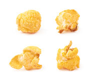 Single popcorn flake isolated. Single cheese flavored orange popcorn flake isolated over the white background, set of four different foreshortenings Royalty Free Stock Photography