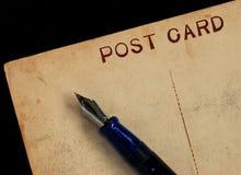 Single Postcard with pen. Antique postcard with a fountain pen Royalty Free Stock Photos