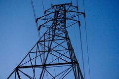 Single Power Line Transmission Tower. A single power line transmission tower, with electrical cables running in both directions. rises up against the background royalty free stock photo