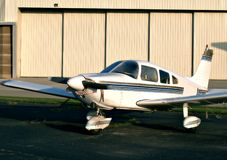 Single Prop Aircraft. Single prop airplane sits in a tie-down area on the airfield in front of a large hangar Stock Photos