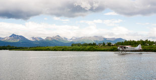 Single Prop Airplane Pontoon Plane Water Landing Alaska. A bush plane performs take off in Alaska with Chugach Mountains in the Background Royalty Free Stock Images