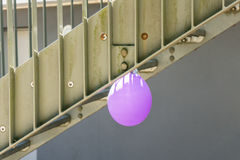 Single purple baloon hanging from a star. Single purple baloon hanging lonely from a stair Royalty Free Stock Images