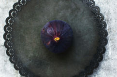 Single purple fig on rustic metal plate, top view Royalty Free Stock Photography