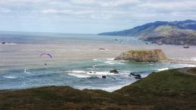 Solitary paraglider & the vast ocean. A single purple kite for paragliding is so small against the largess of the surrounding cliffs and sea. Intense colors Stock Photos