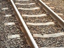 Single railways and chock and gravel. Yellow sunlight Stock Photos
