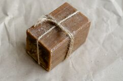 A single rectangular piece of new soap wrapped with twine