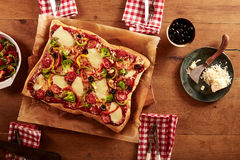 Single rectangular pizza with various ingredients Stock Photography