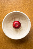 Single red apple in a bowl. Looking down on a single red apple in a white bowl royalty free stock image