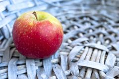 Single Red Apple in a Gray Wicker Basket. Copy Space.  royalty free stock photos
